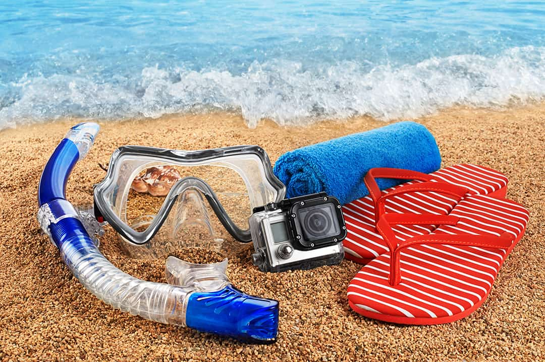 Snorkel and go pro camera on the beach.