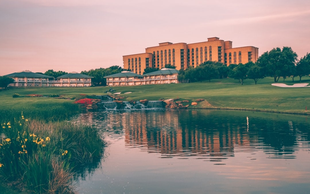 View from golf course over pond of Four Seasons Las Colinas Dallas building