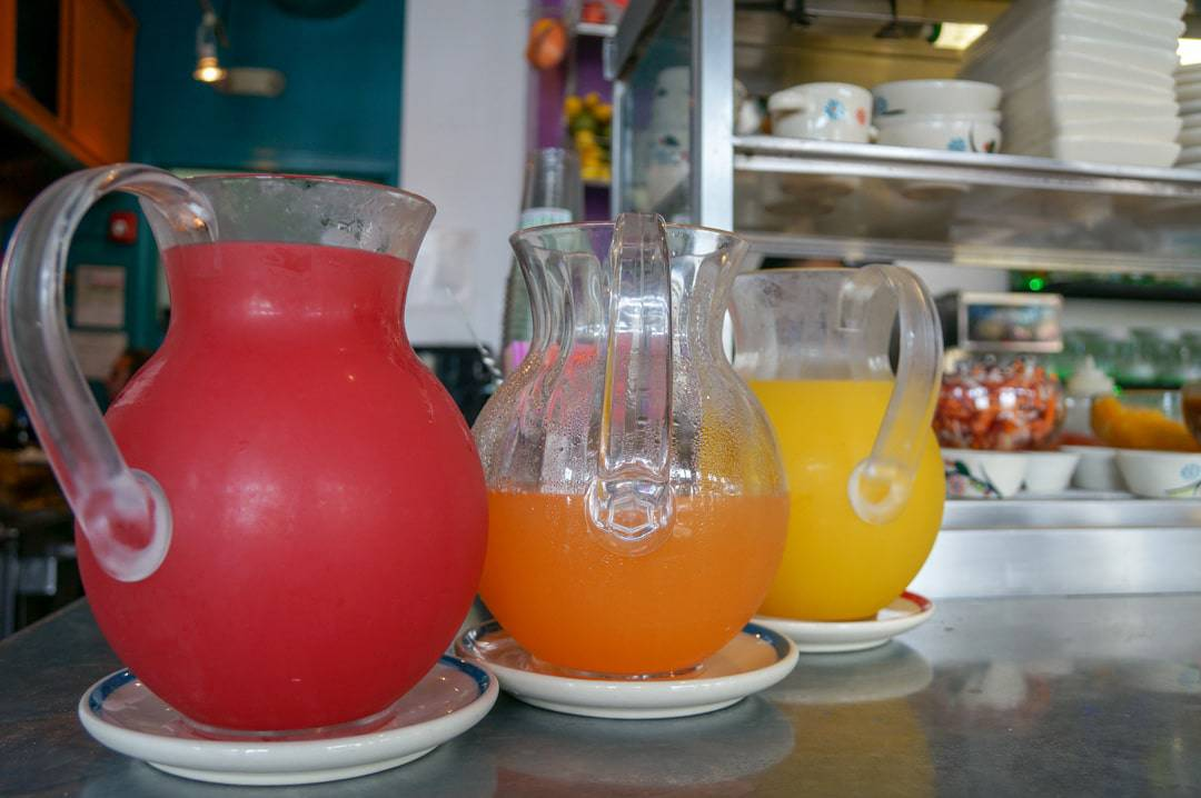 Fresh juices on display La Fruteria Restaurant counter filled with fresh food.