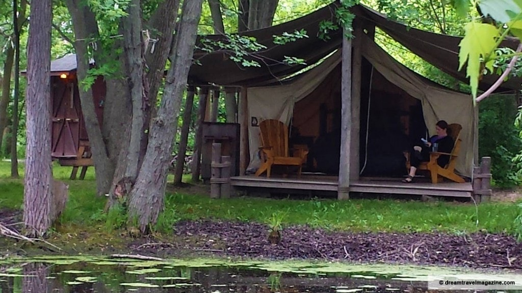 Prospector's tent at Oakwood Escape in Dunnville Ontario with queen size bed inside, next to a pond