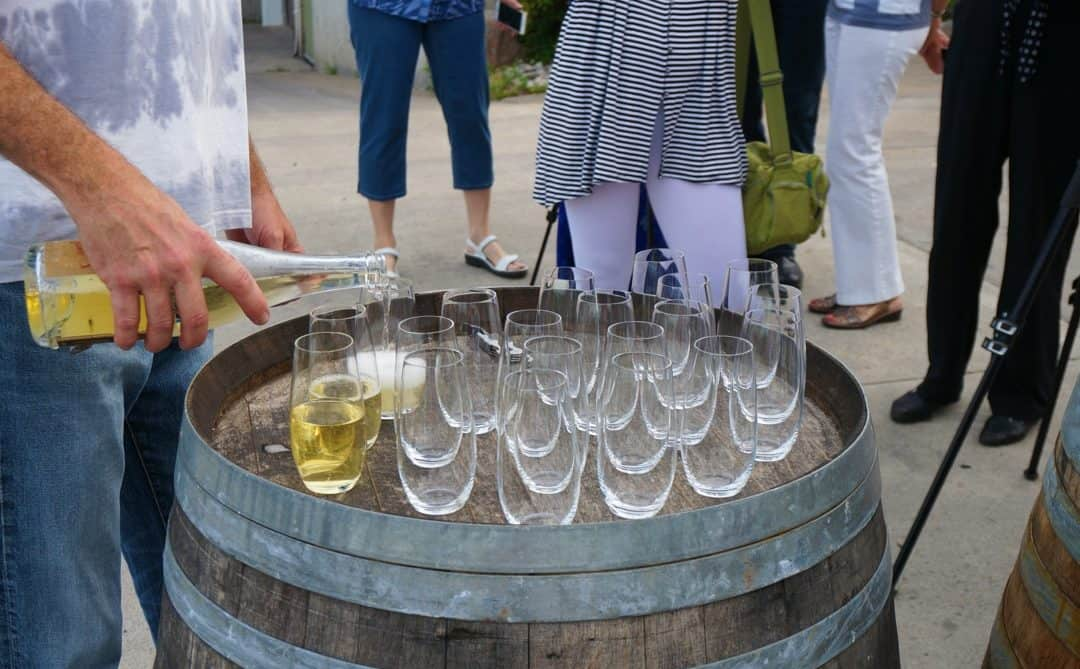 Creekside Winery wine tasting winemaker rob power pours white wine into glasses sitting on a barrel.