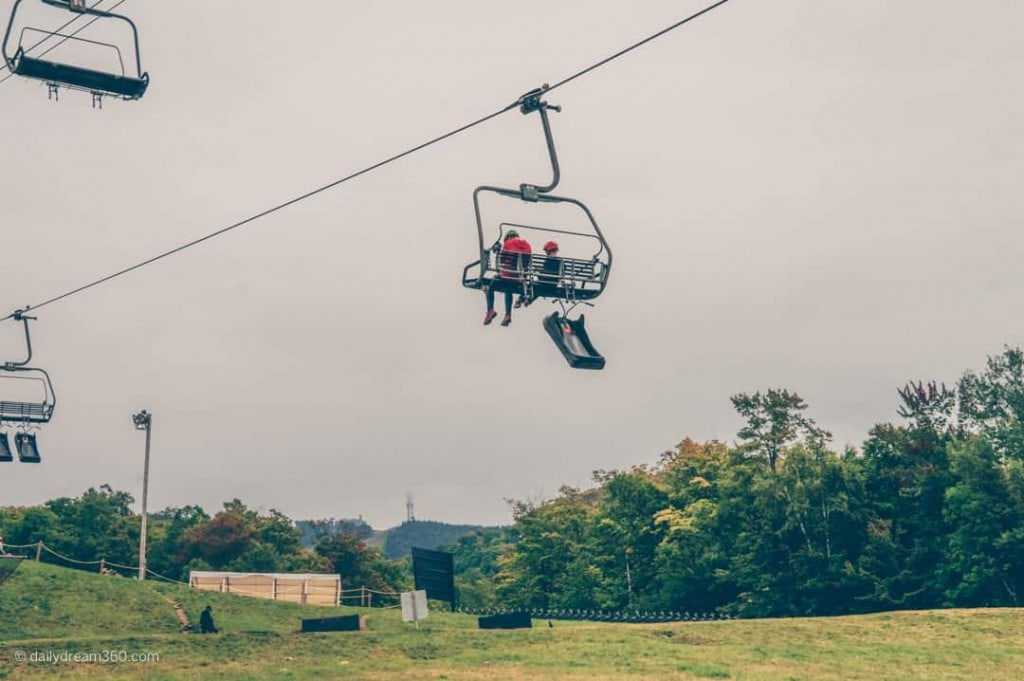 People on ski lift with luge hanging below at Tremblant