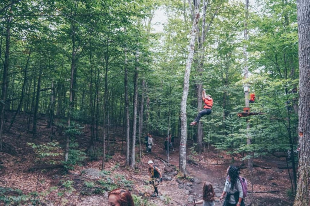 People zip lining with onlookers on trail below at Tremblant Resort