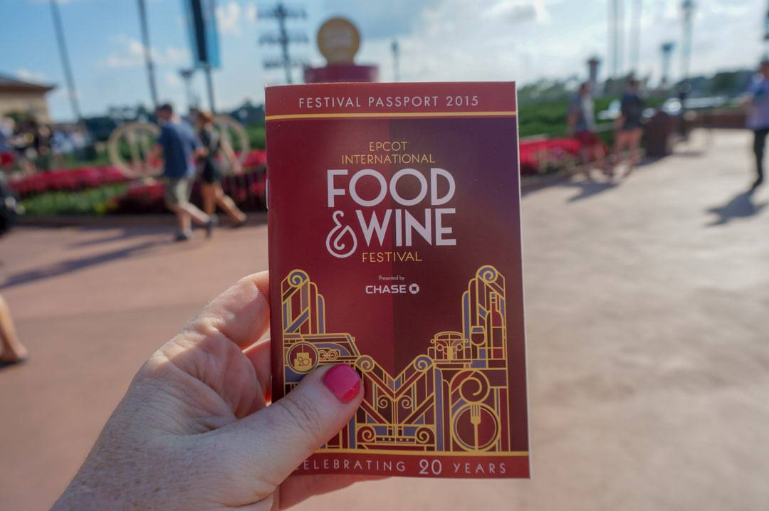 Epcot food and wine festival passport looking held up with the park behind it.