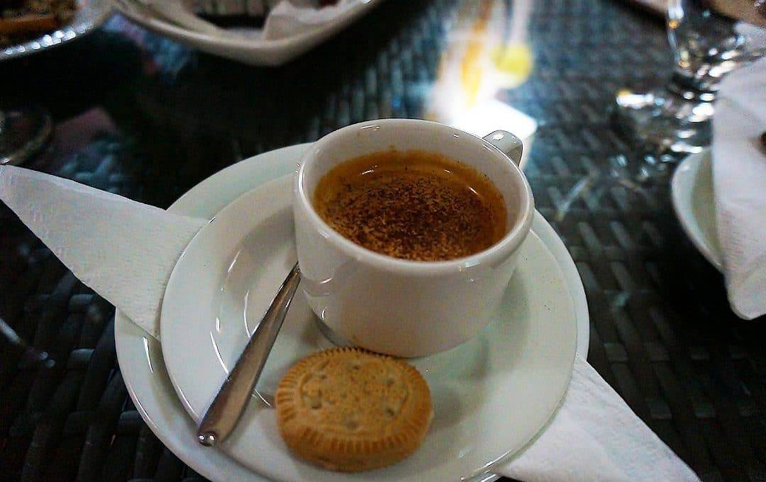 Coffee with biscuit on table at Constantin Cafe Santiago de Cuba