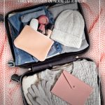 Winter clothing in suitcase on pink bedspread with text How to Pack Light for Winter Travel with This Winter Clothing ListHow to Pack Light for Winter Travel with This Winter Clothing List. (pin image)