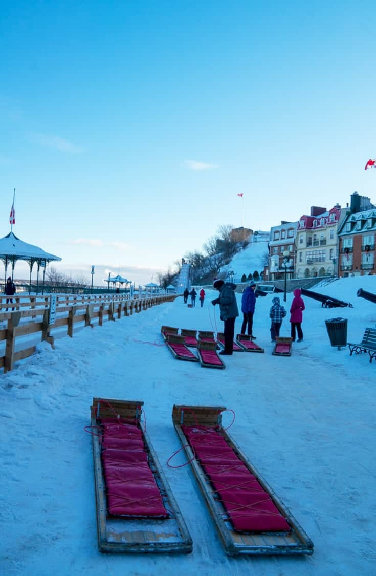 Planning a winter trip to Quebec City? One of its most popular attractions is the famous 1884 Quebec City Toboggan Ride located on the Dufferin Terrace boardwalk within the Old City. | Quebec City | Toboggan Ride | Quebec | Attraction | Canada | Travel | Winter |