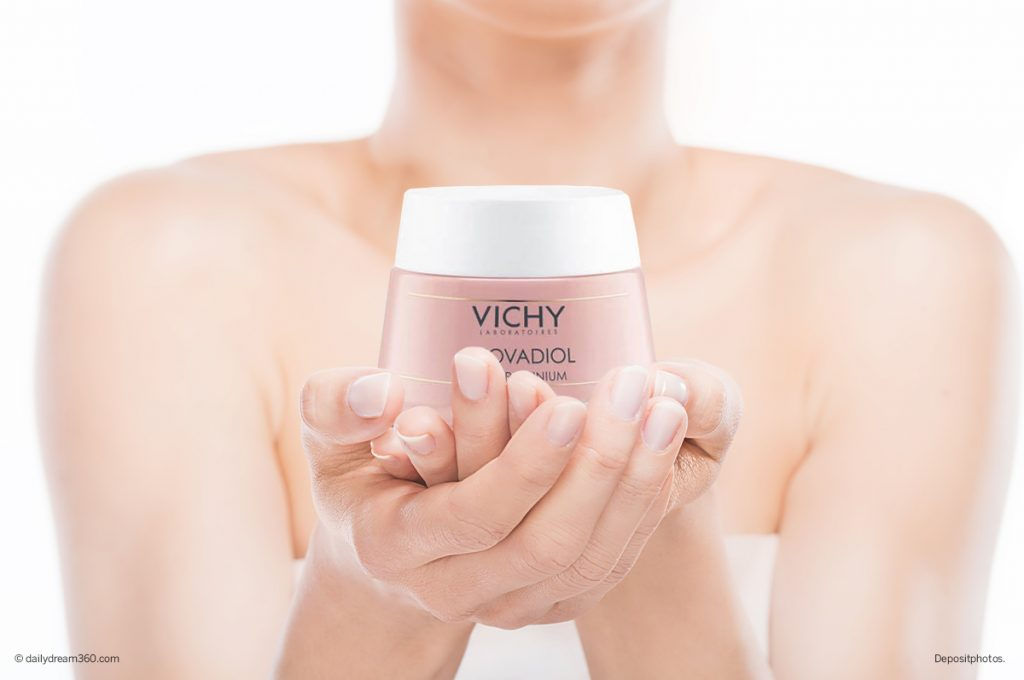 Mature woman holding bottle of Vichy Neovadiol cream