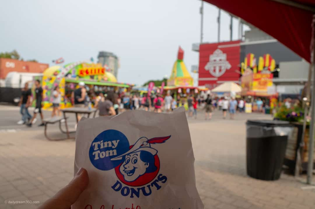 Tiny toms donut bag held in front of CNE midway