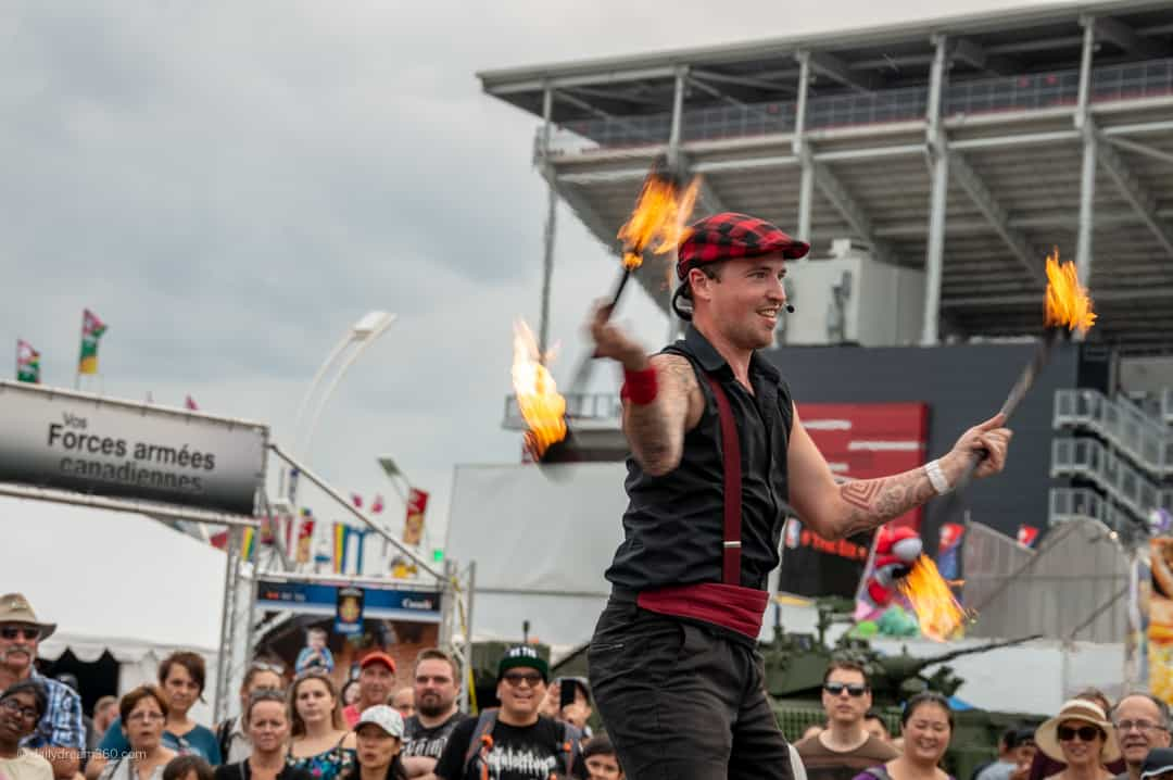 performer juggles with fire batons at CNE