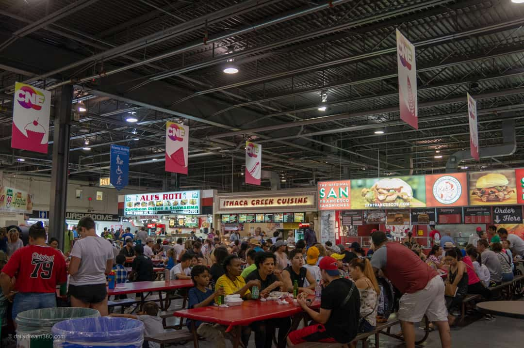 Inside the food buildings people eating with vendors around them at CNE 2018