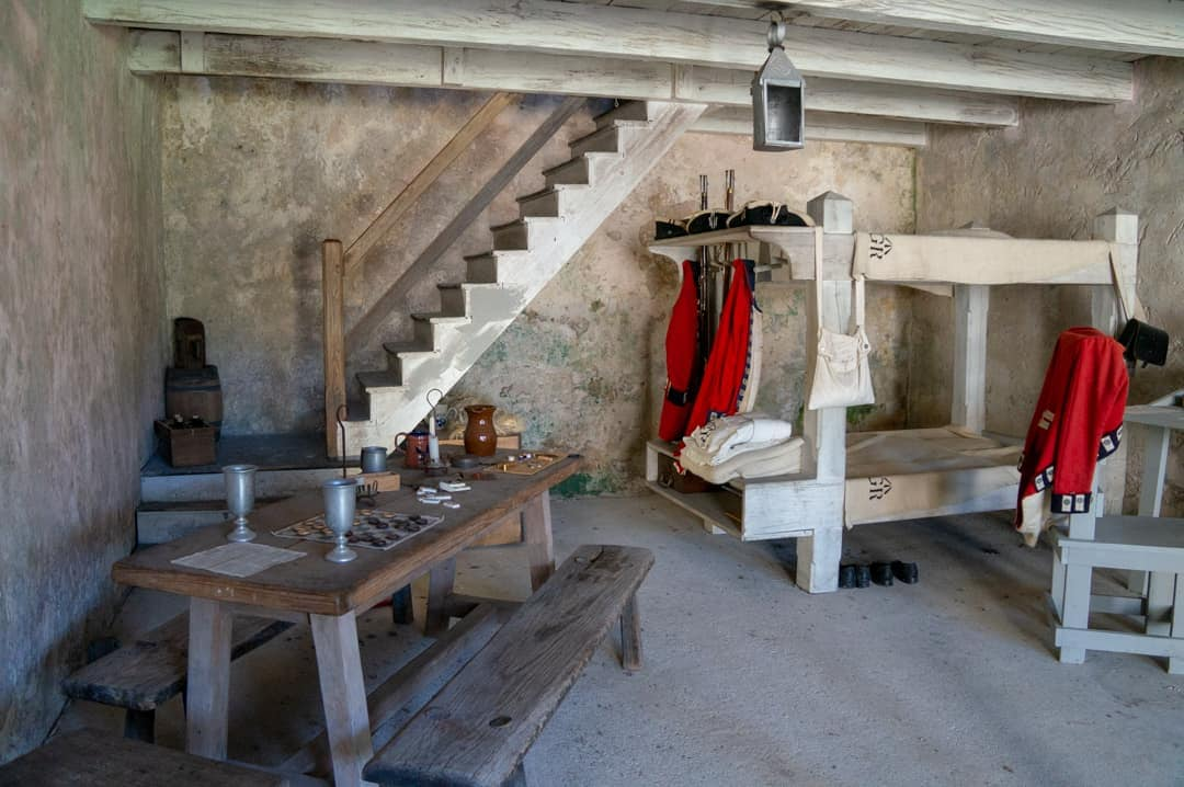 One of the historic rooms depicting a soldiers quarters in the Castillo de San Marcos St Augustine. A jacket hangs on a bed with a table on display.