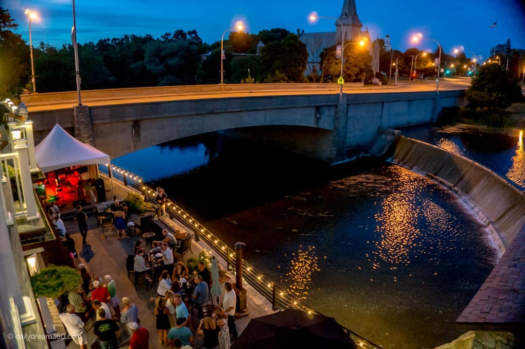 Patio bar with live music playing and view of creek at Farmer's Creekside Tavern & Inn