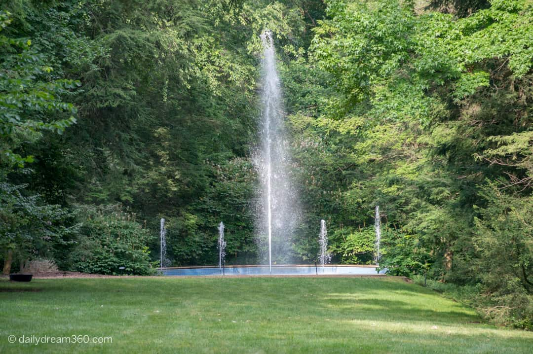 water fountain amongst trees shooting water at Longwood Gardens PA