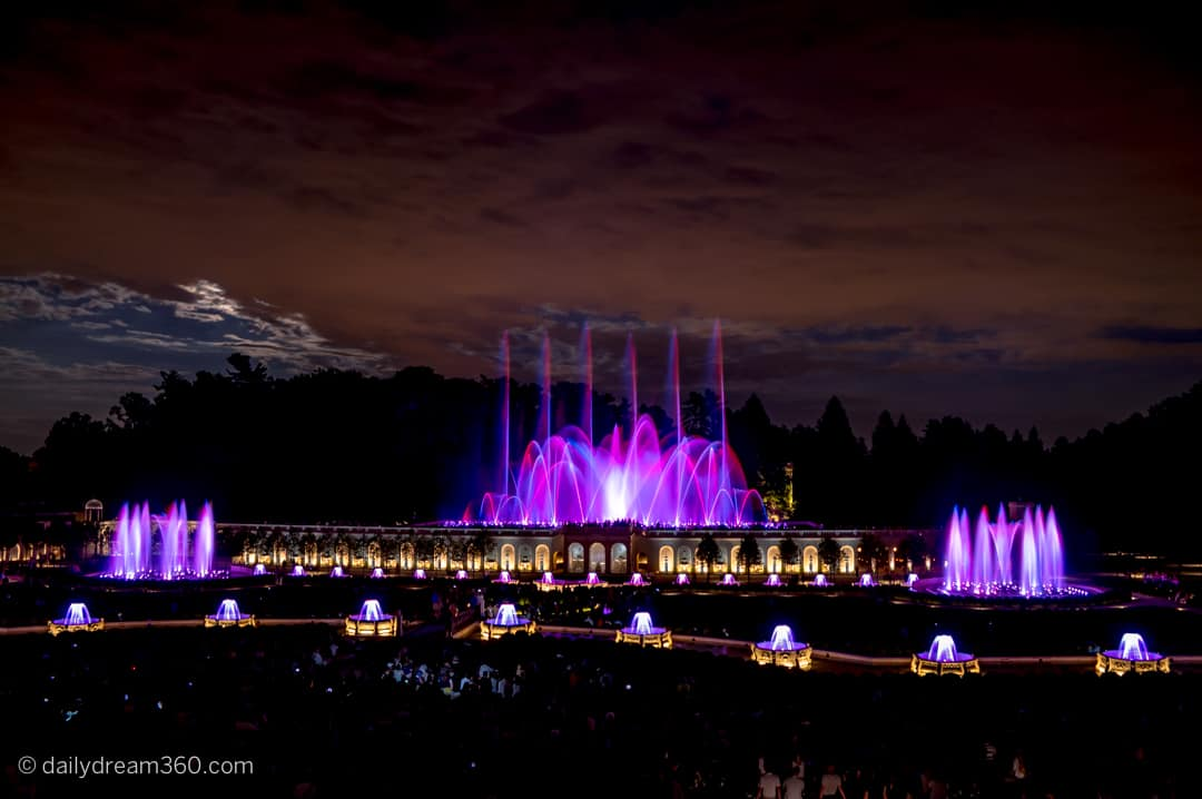 Night fountain show with water fountains lit in pink, purple as they move to music