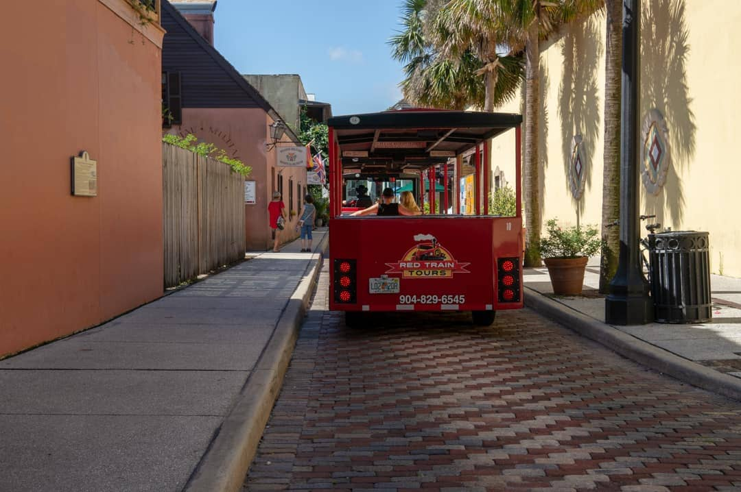 Red train squeezes through narrow street in st augustine historic village