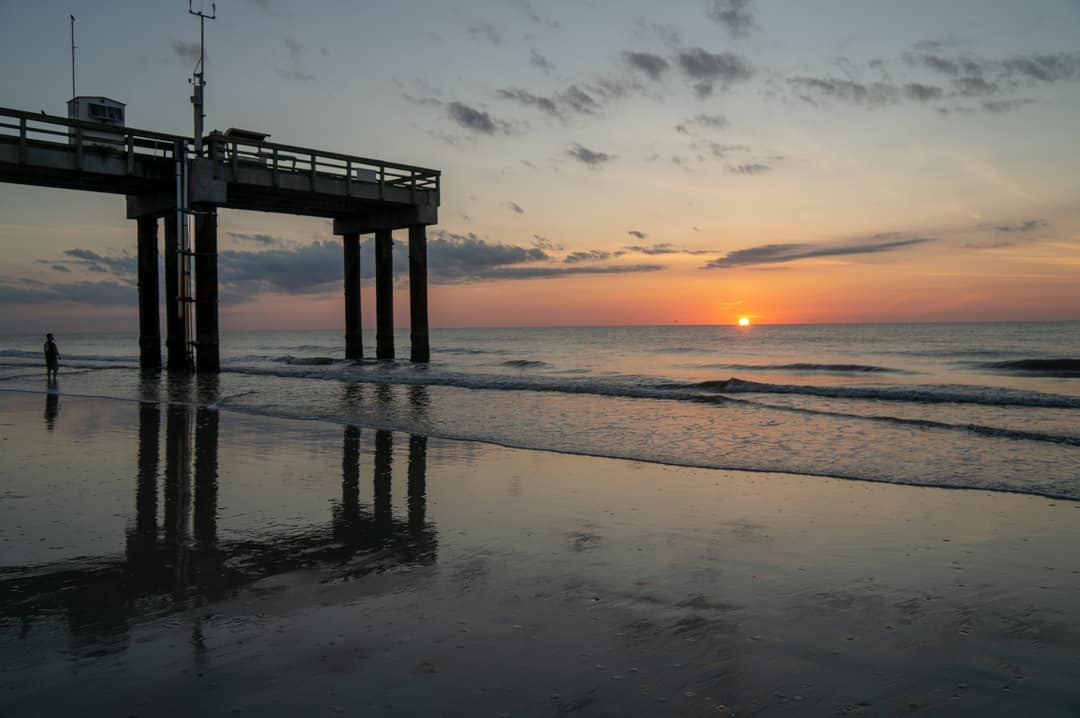 Sunrise over the ocean next to pier on the beach in St Augustine Beach Florida