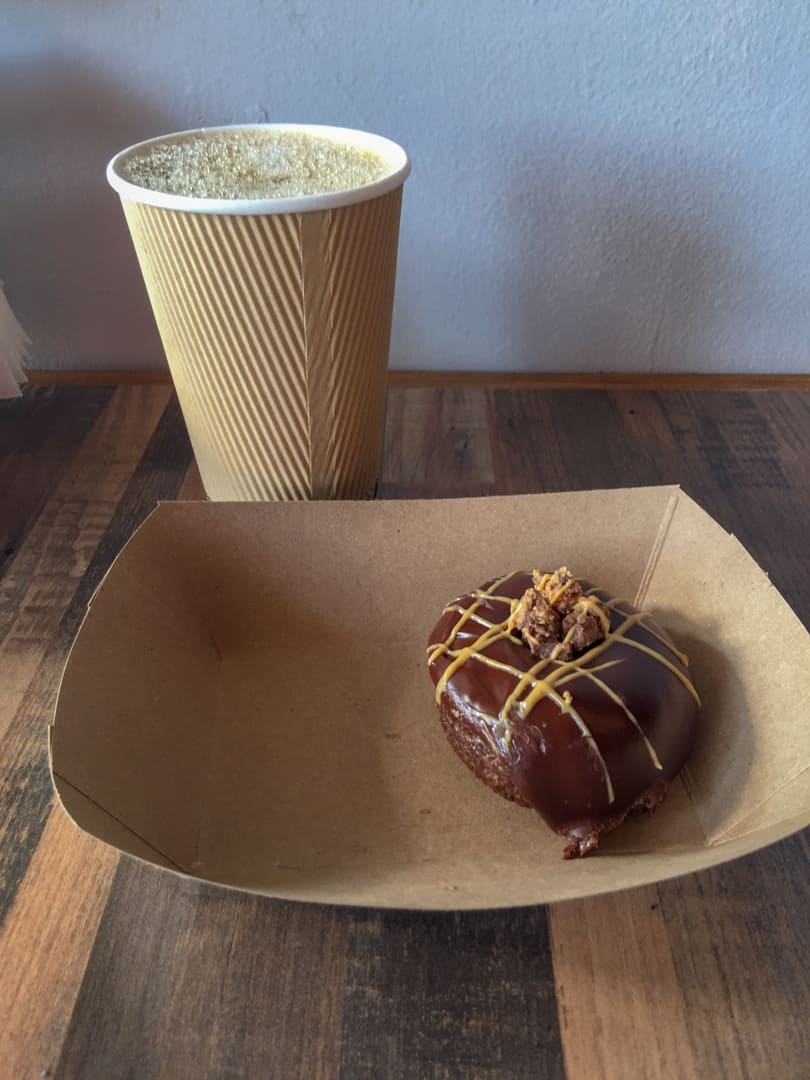 Donut and coffee on counter at Swillerbees Craft Donuts & Coffee Bar
