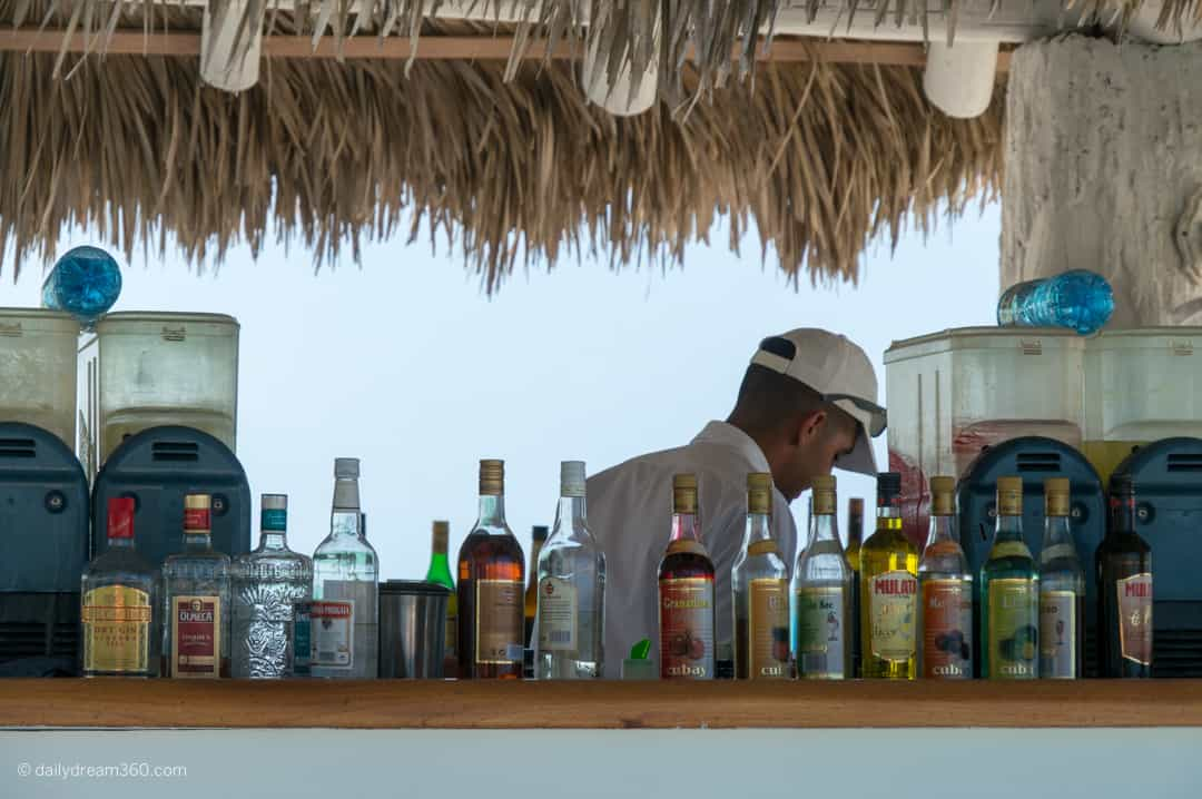 Beach bar bottles lined up on bar as barman works behind