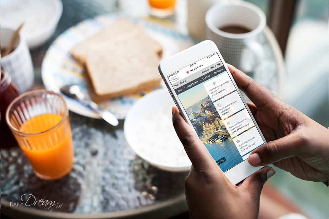 woman holding iPhone with air canada app open over breakfast table with toast and juice
