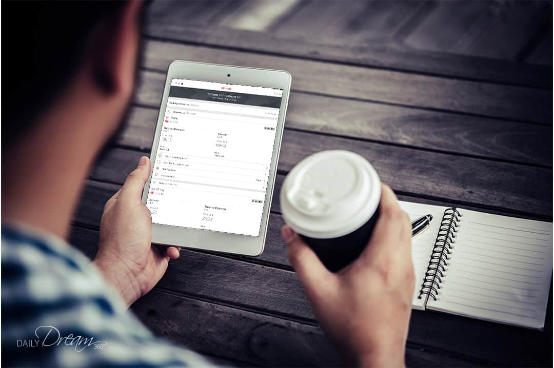 Man holding iPad with air canada app open and holding a coffee