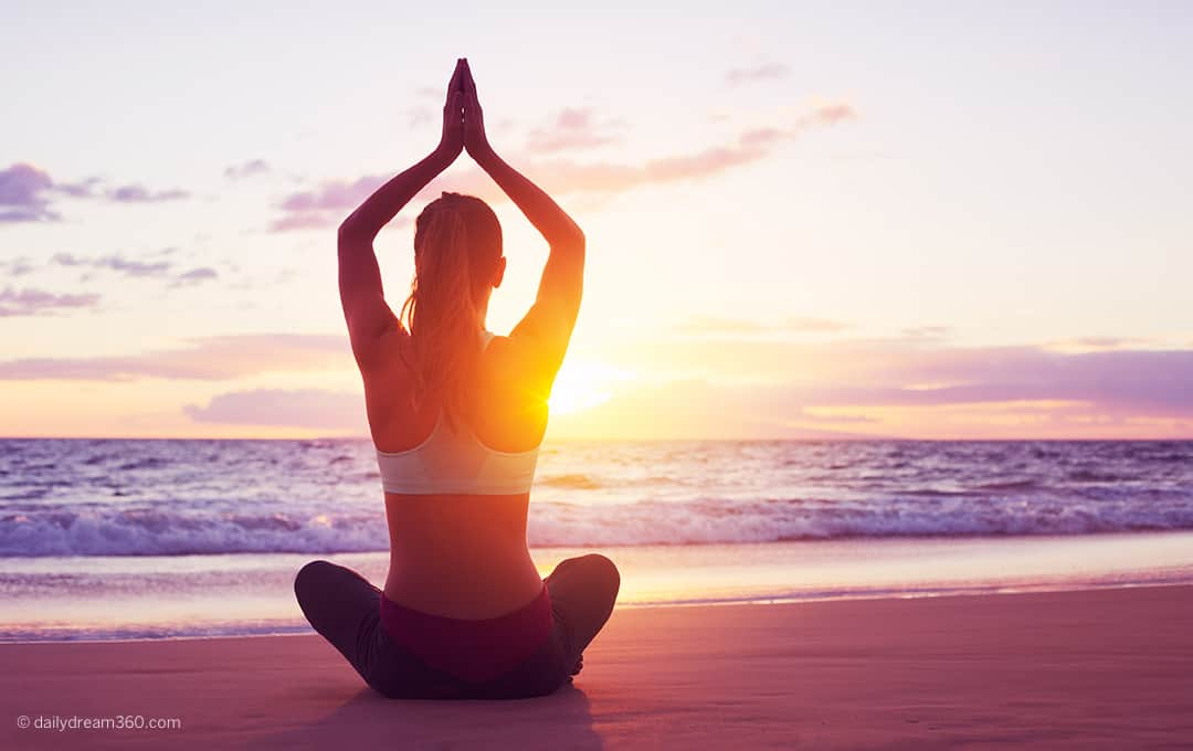 Stock image of woman doing yoga on beach at sunset