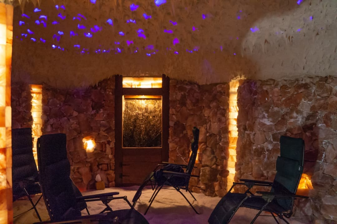 inside salt cave three chairs with purple lights in ceiling