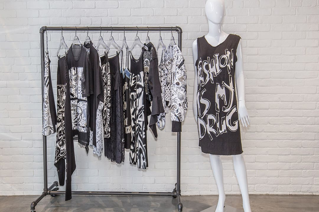 Rack inside RockNKarma store featuring black clothes with white wording on top