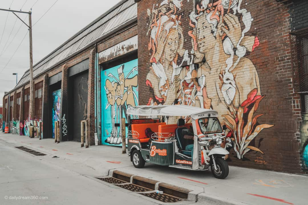 eTuk vehicle parked in front of street art wall in RiNo Neighbourhood