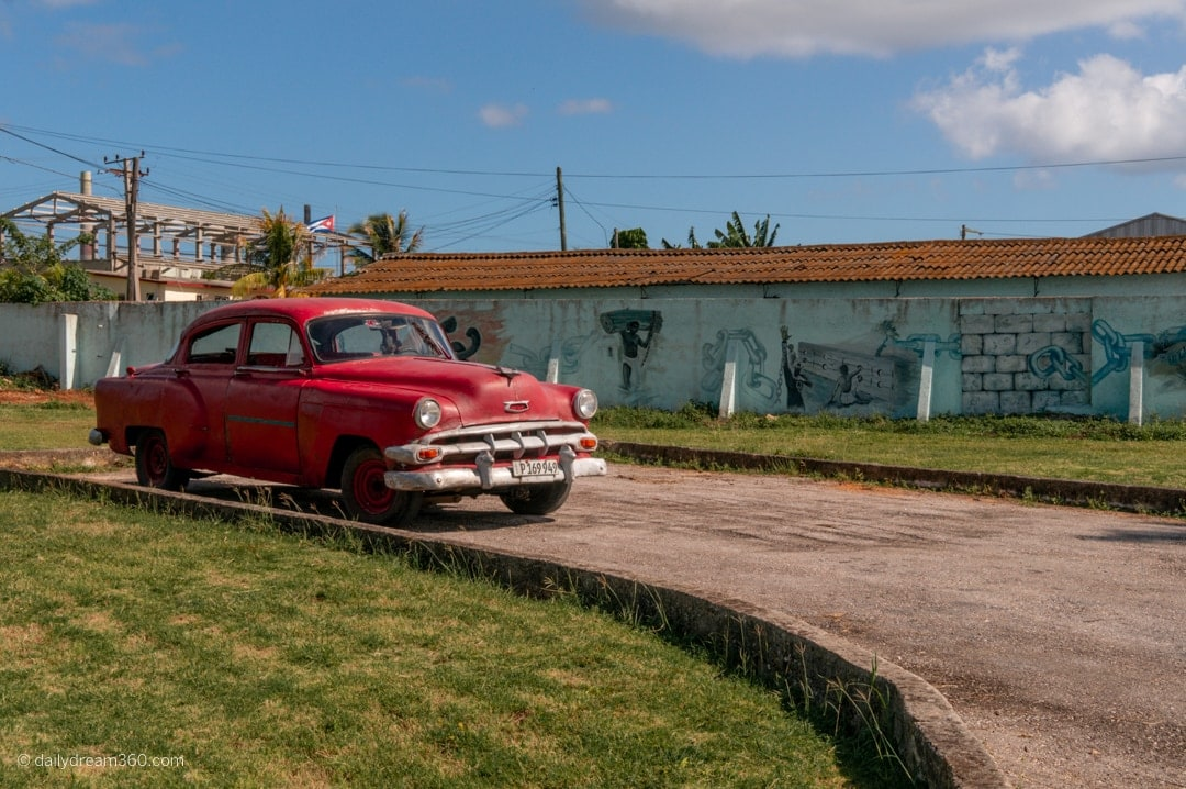 Old red car sits outside the castle in matanzas cuba