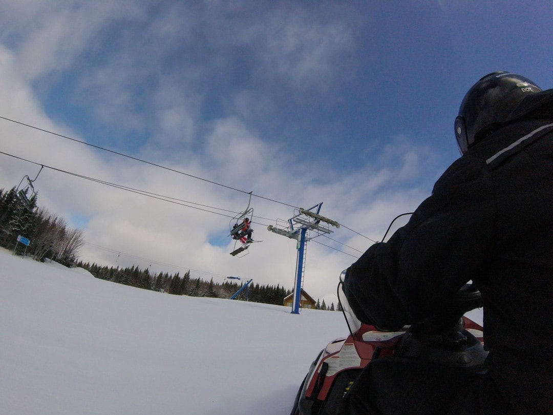 snowmobile on ski hill with chairl lift