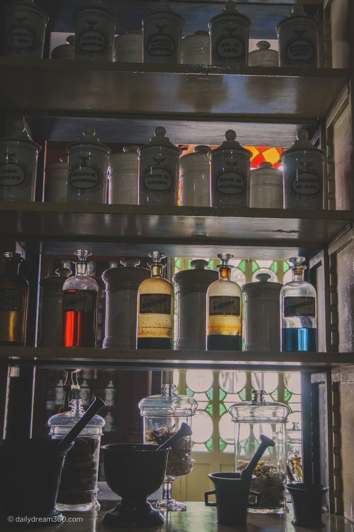 Bottles on shelf lit up by window at Pharmaceutical Museum Matanzas Cuba