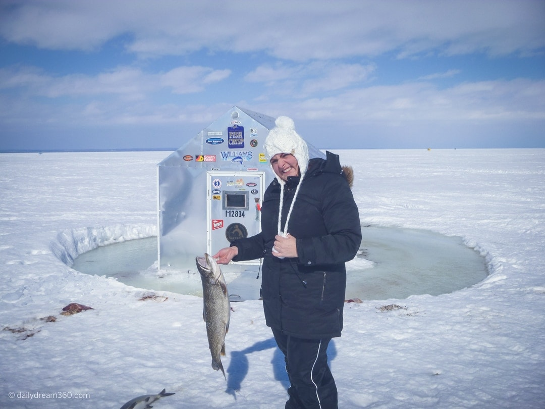 Sharon Mendelaoui holding fish in front of ice hut on Lake Simcoe.