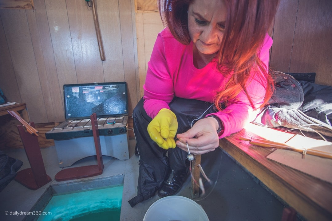Sharon Mendelaoui setting up fishing line in ice hut