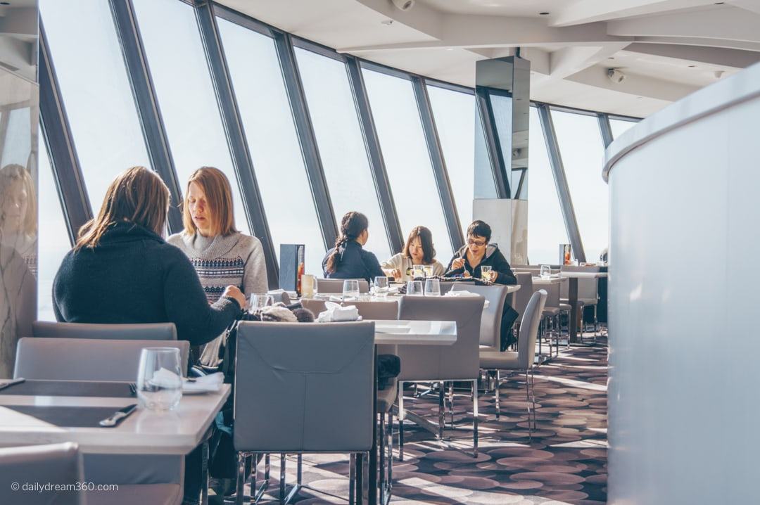 People sitting by windows at 360 restaurant in CN Tower Toronto