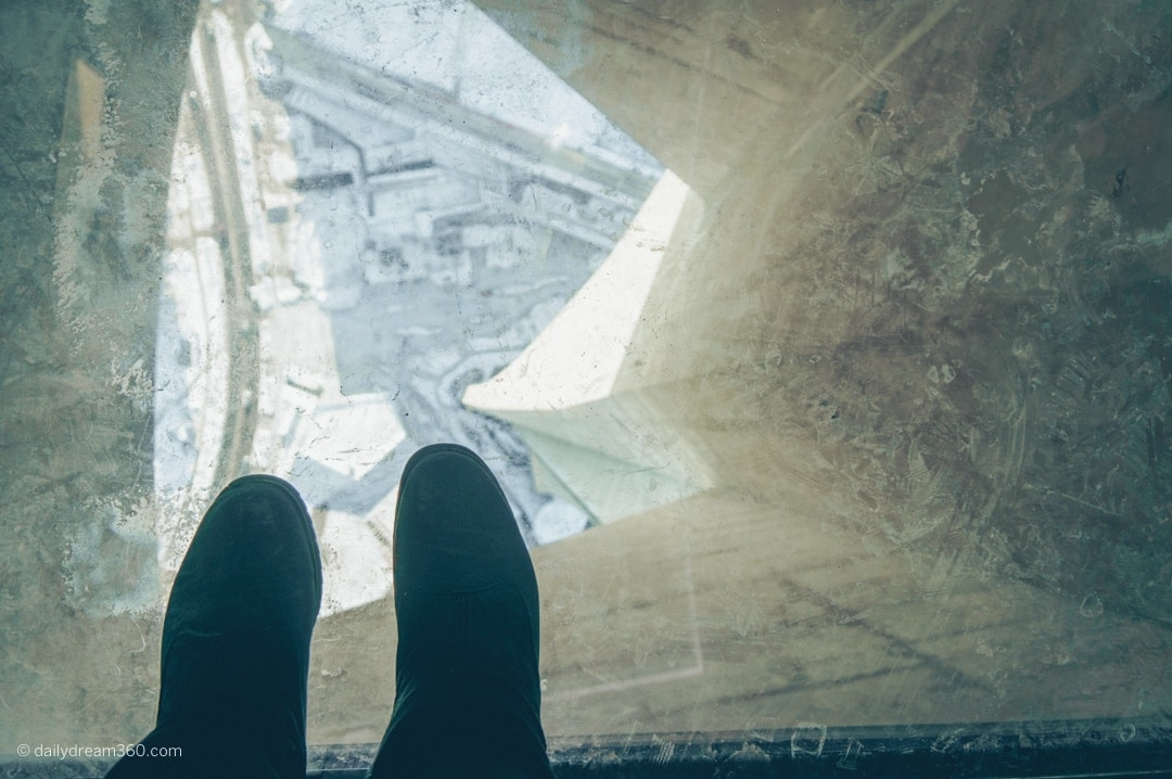 Feet on glass floor looking down CN Tower