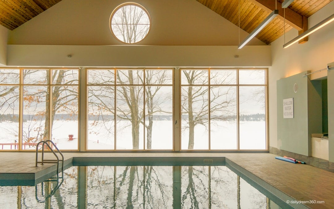 View inside indoor pool looking out to frozen lake at Viamede Resort Ontario Winter Weekend Getaway