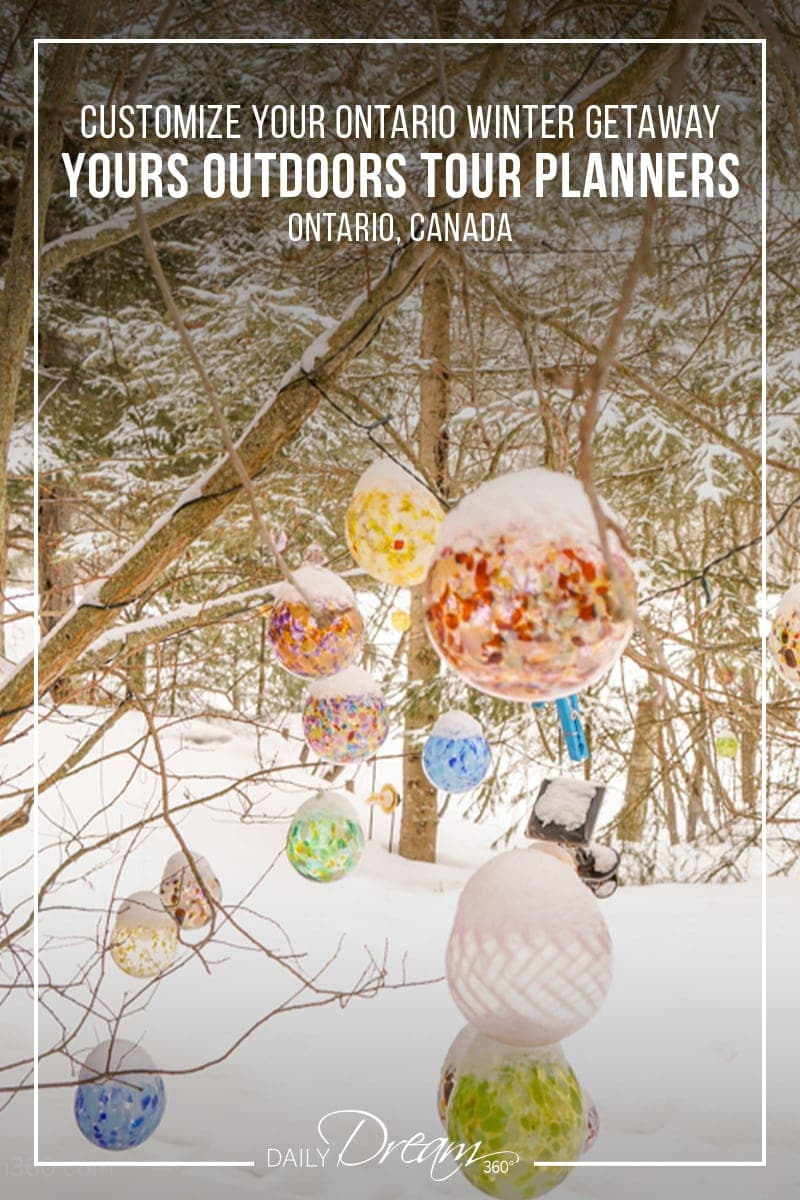 Glass balls covered in snow hang from trees at Artech Glass Studio in Haliburton