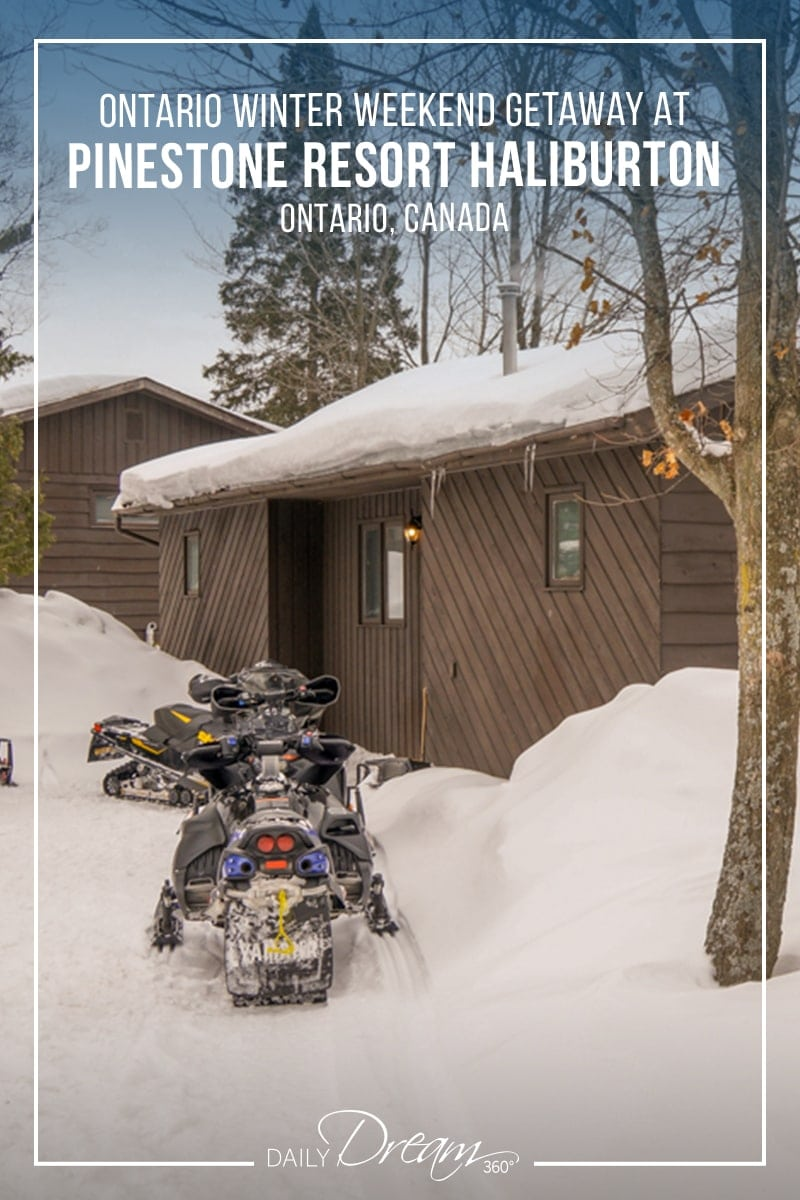Snowmobiles parked outside cabins at Pinestone Resort Haliburton in Winter