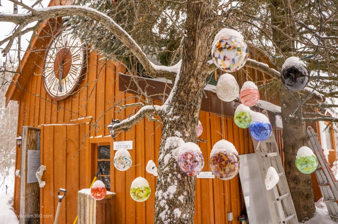 Outside the glass blowing workshop at artech glass in Haliburton, glass balls hang in tree during winter.