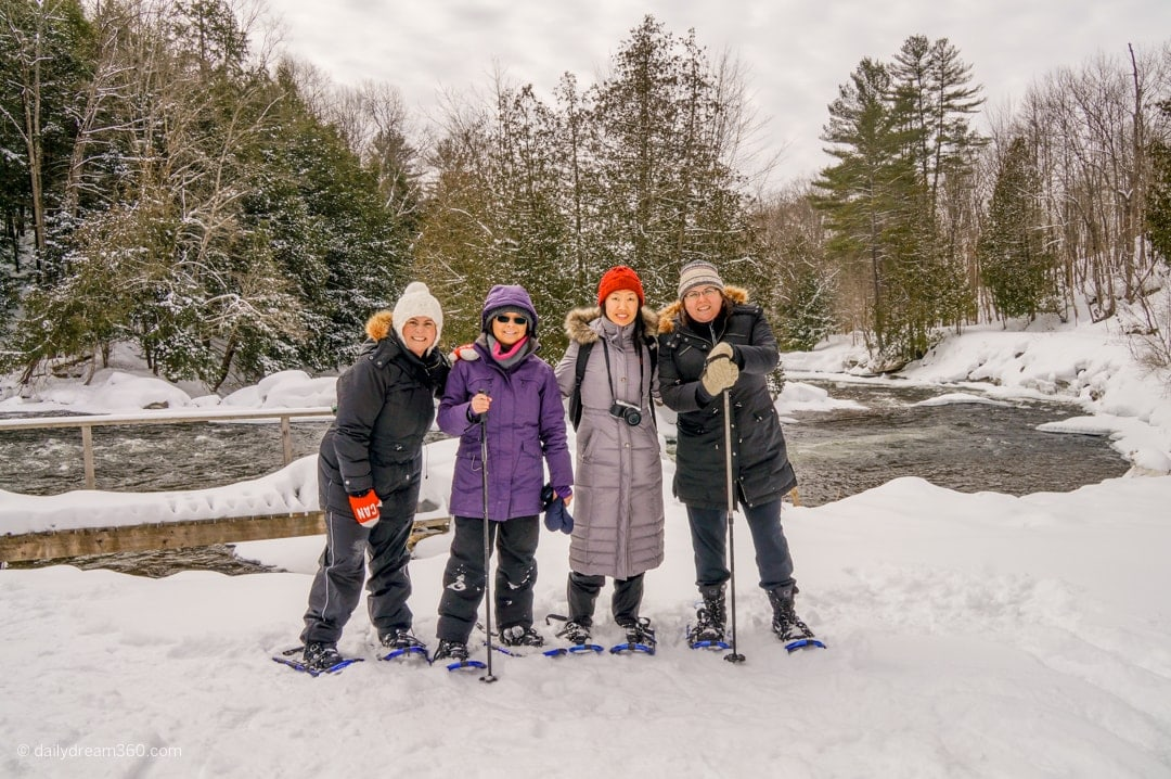 The girls stand in front of river part of the Yours Outdoors winter weekend getaway in Haliburton