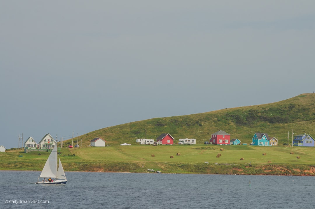 Iles de la Madeleine sailboat floating in front of green hill with colourful houses