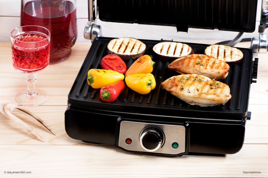 Indoor electric grill with chicken and vegetables cooking