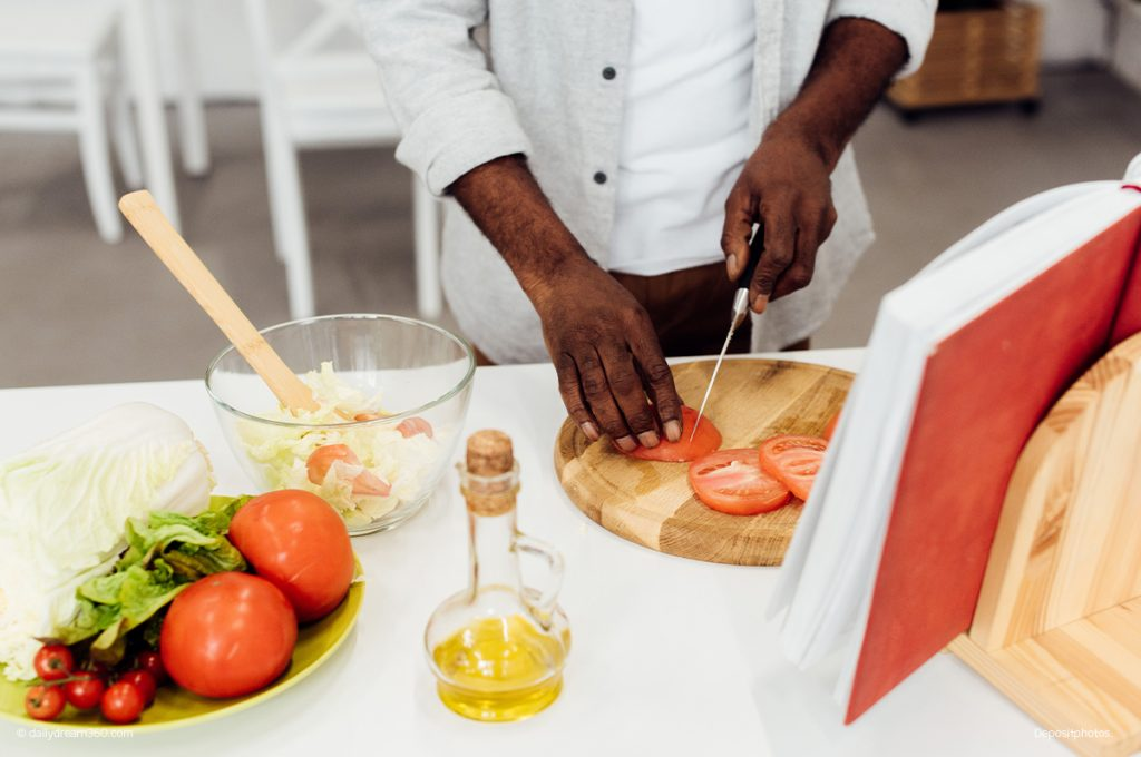 man cutting tomatoes in from of cookbook
