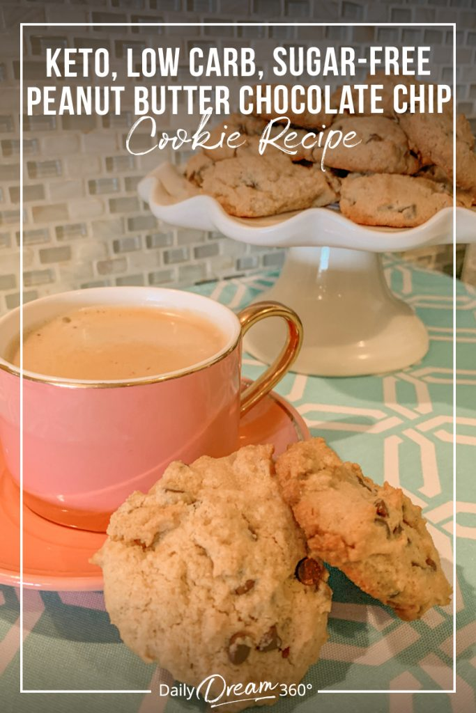 Pink coffee cup with cookies and tray of cookies in background with text Keto Low Carb Sugar Free Peanut Butter Chocolate Chip Cookies