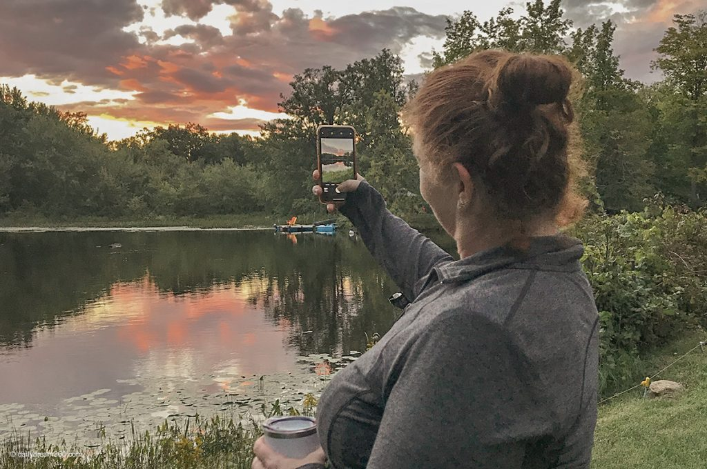 Sharon taking photo of sunset by the lake
