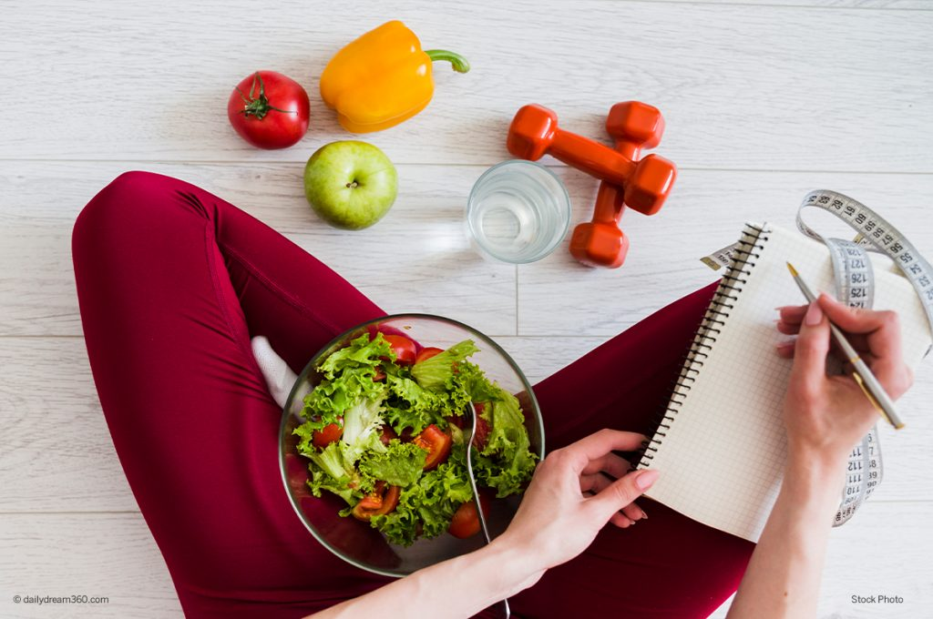 Woman with salad in lap taking notes
