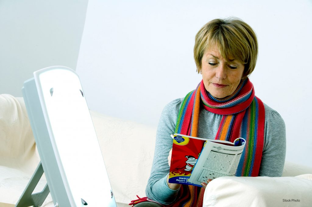 Older woman sitting and reading magazine next to a light therapy box