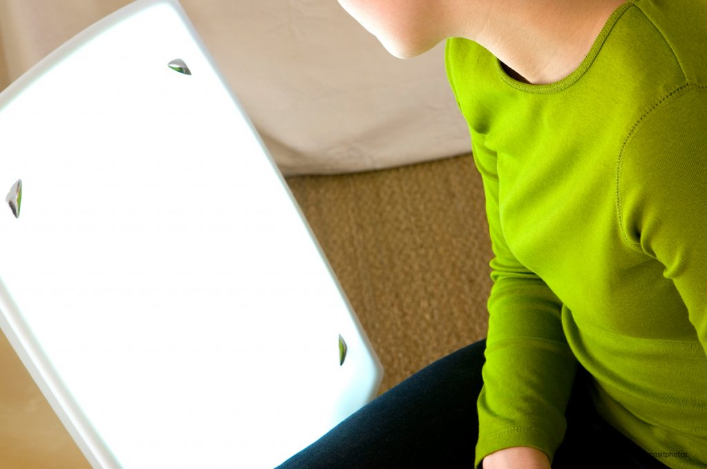 woman in green top looking at light therapy lamp