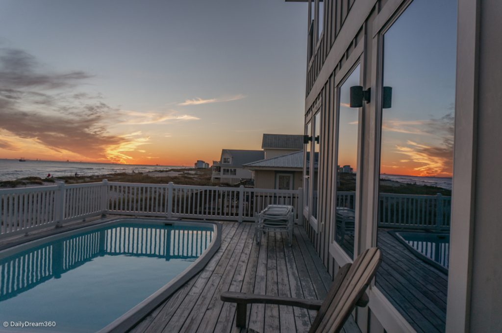 Sunset reflected on beach house window overlooking pool and beach in Gulf Shores Alabama